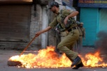 An Indian policeman removes a burning tyre from the road in Srinagar after protesters attempted to block the road to hamper the movement of Indian forces [Showkat Shafi]