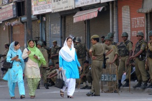 Kashmiri women walk past Indian paramilitary soldiers on a road in Srinagar [Showkat Shafi]