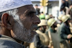 A Kashmiri man attends a rally in Srinagar as Indian policemen stand guard in the background [Showkat Shafi]