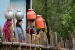 Kashmiri women carry water in vessels in Dardpora village in the Kupwara district. Almost the entire male population of this village was killed during the early years of the conflict [Showkat Shafi]