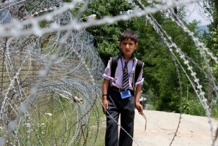 A Kashmiri boy walks past concertina wires placed outside an Indian military camp in the Kupwara district of northern Kashmir [Showkat Shafi]